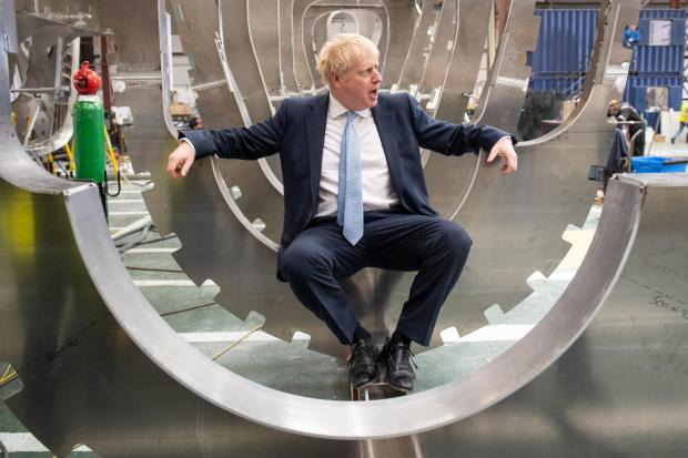 Conservative party leadership contender Boris Johnson sits inside a boat under construction