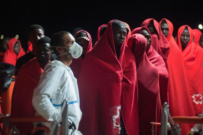 A group of migrants stand on a rescue vessel as they wait to disembark after their arrival at the Port of Malaga