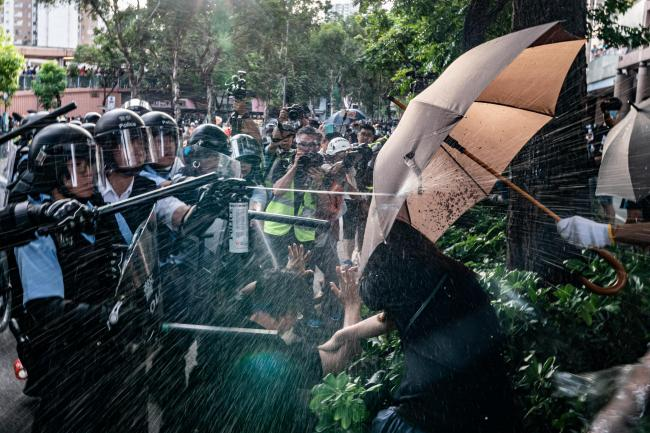 Police officers use pepper spray to disperse protesters in a July protest