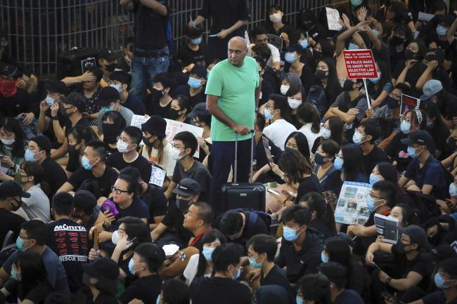 A traveller stands amidst protesters during a sit-in rally at the Airport in Hong Kong