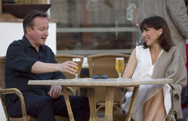 Is David Cameron (pictured with his wife Samantha) basking on a beach somewhere?