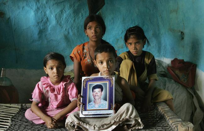 Children near Nagpur, India, mourn the death of their father from suicide by pesticide