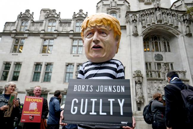 A protester wearing a Boris Johnson mask outside the Supreme Court in London