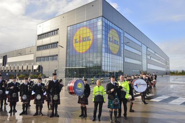 North Lanarkshire Schools Pipe Band and Lidl's Head of Supply Chain, Euan Fitzpatrick (green kilt) officially open operations at its new Regional Distribution Centre