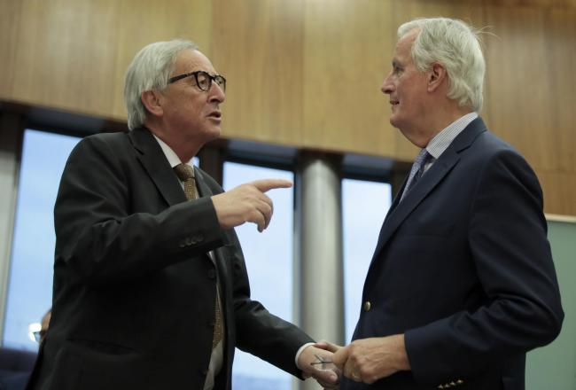 European Union chief Brexit negotiator Michel Barnier, right, speaks with European Commission President Jean-Claude Juncker