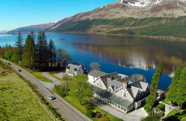 The Whispering Pine Lodge overlooks the water of Loch Lochy