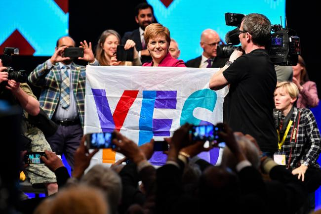 Nicola Sturgeon holds a Yes flag following her address to the party autumn conference