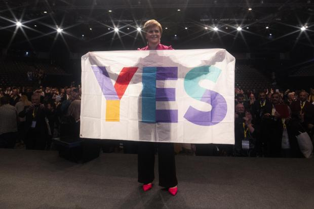 The National: Nicola Sturgeon with a Yes banner
