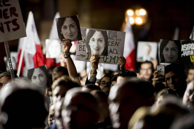 Protesters hold photos of Daphne Caruana Galizia during a protest outside the office of the Prime Minster of Malta by civil groups Occupy Justice and Republica in Valletta, calling for the resignation of Malta Prime Minister Joseph Muscat