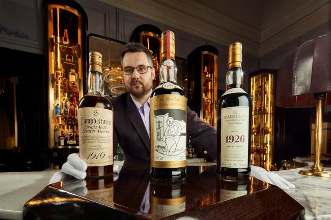 Whisky Auctioneer founder Iain McClune with some of the bottles from the collection
