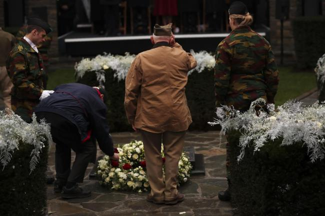 US Battle of the Bulge veterans put flowers to pay tribute during a ceremony to commemorate the 75th anniversary of the Battle of the Bulge at the Mardasson Memorial in Bastogne, Belgium