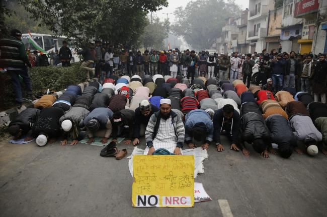 Indian Muslims pray on a road with a sign protesting the National Register of Citizens