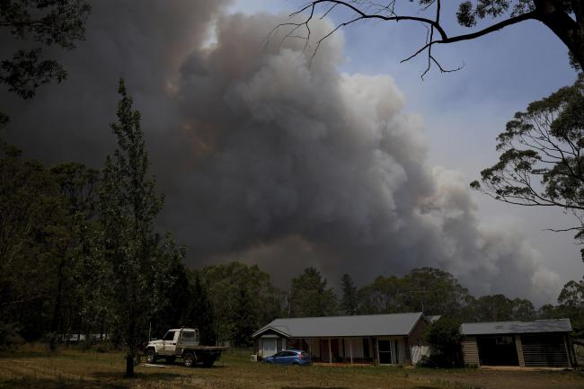 A home stands as smoke from the Grose Valley fire rises in the distance in Bilpin, west of Sydney. Australia s most populous state has been paralysed by catastrophic fire conditions amid souring temperatures as wildfires also ravaged the country's sou