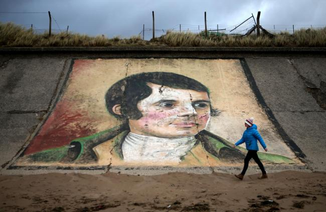 A person walks past a mural of Robert Burns on the sea wall at Ardeer beach, near to his birthplace of Alloway in Ayrshire