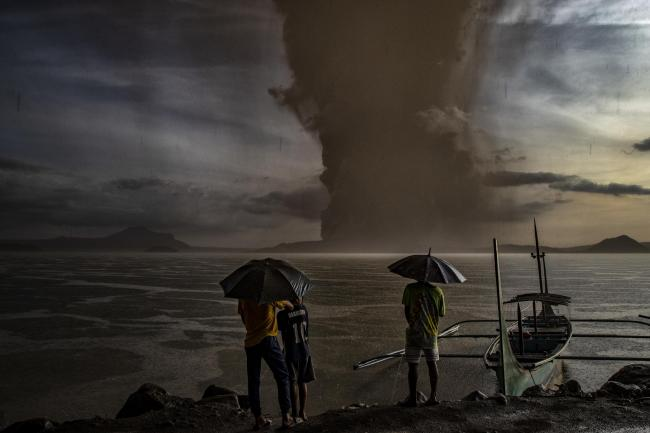 Residents look on as Taal Volcano erupts in Talisay, Batangas province, Philippines
