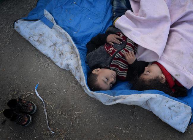 Migrant children sleep at a camp in North Macedonia