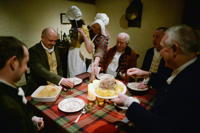 A group re-enact the first ever Burns Supper held in 1801 on the fifth anniversary of his death inside the cottage where he was born in 1759