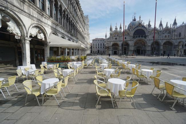 Empty chairs and tables are lined up outside a restaurant in St. Mark's Square in Venice