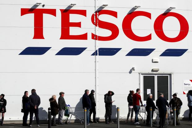 The National: People queue outside a Tesco Extra store in Madeley, Shropshire
