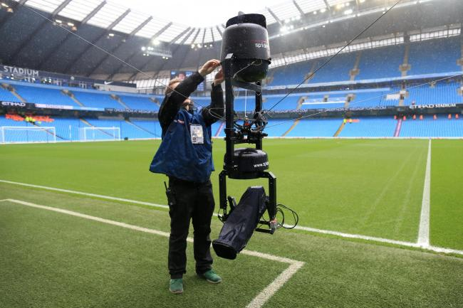 A cameraman sets up his equipment at the Etihad Stadium