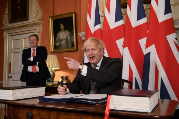 The National: UK chief trade negotiator David Frost looks on as Prime Minister Boris Johnson signs the EU-UK Trade and Cooperation Agreement at 10 Downing Street
