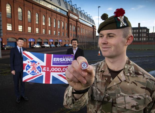 The National: Black Watch squaddie Callum Robson displays the first ever RSEA pin badge sold to raise funds for Erskine, with RSEA president Gordon Smith alongside Erskine chief executive Ian Cumming