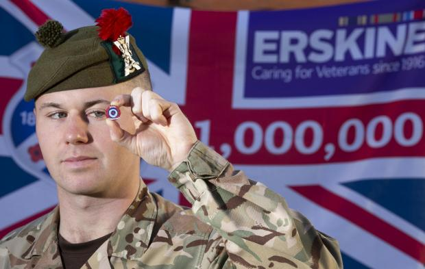 The National: Black Watch squaddie Callum Robson displays the first ever RSEA pin badge sold to raise funds for Erskine