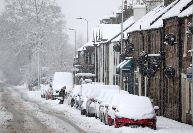 A person clears snow in Braco, near Dunblane. Photograph: PA