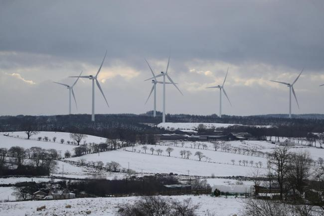 Wind turbines spinning atop snow covered hills around Avonbridge, near Falkirk