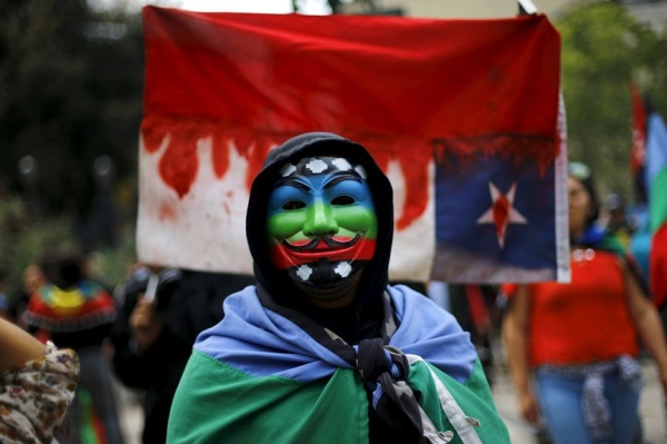 A Mapuche Indian activist wears a Guy Fawkes mask painted with the Mapuche flag at a protest in Santiago, Chile