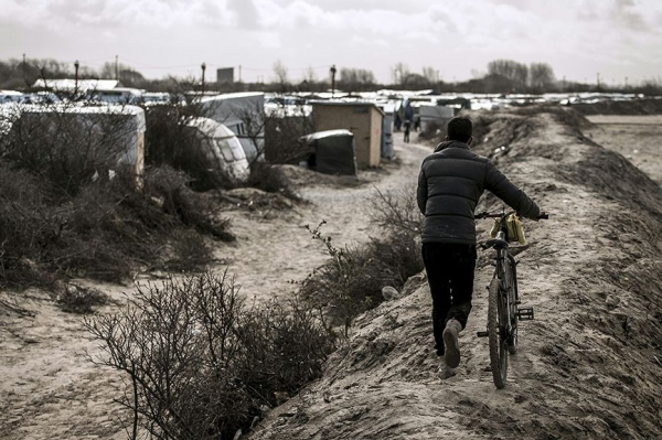 A migrant boy pushed his bicycle alongside the refugee camp at Calais that has been dubbed The Jungle