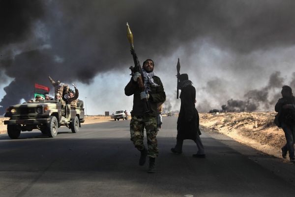 Libyan rebels battle government troops as smoke from a damaged oil facility darkens the sky during the 2011 fighting