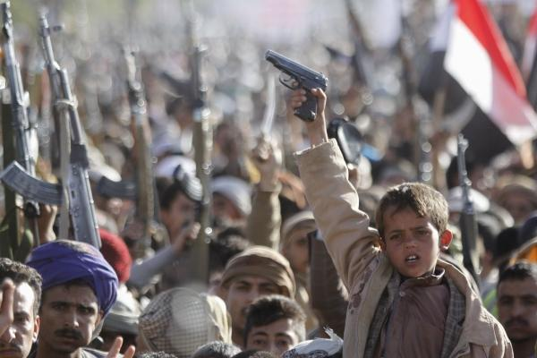 A boy raises a gun during a protest in the Yemeni capital Sanaa against Saudi-led air strikes