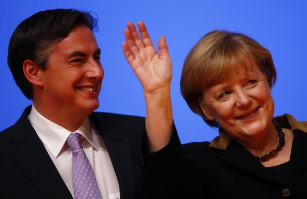 The National: German Chancellor and leader of Germany's Christian Democratic Union (CDU), Angela Merkel and Lower Saxony's Prime Minister David McAllister acknowledge the applause of the delegates after her speech at the CDU's annual party meeting in Hanove