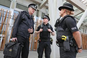 Chief Constable Philip Gormley (left) talks to officers with tasers outside the Scottish Parliament