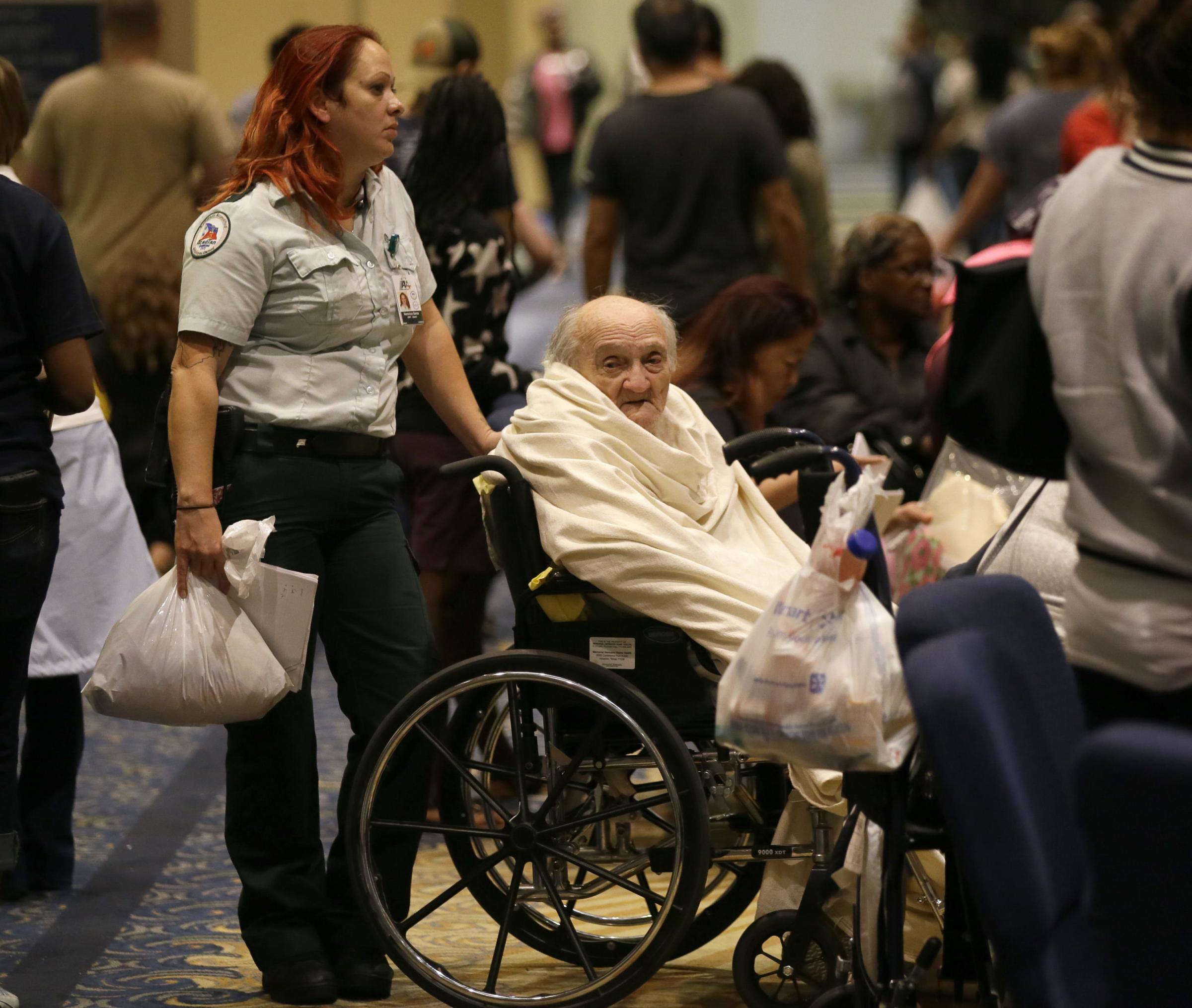 Evacuee Teddy Gifford, 90, waits for a medical evaluation with first responder Veronica Garza at the Lakewood Church in Houston, Texas. Photograph: AP Photo/LM Otero