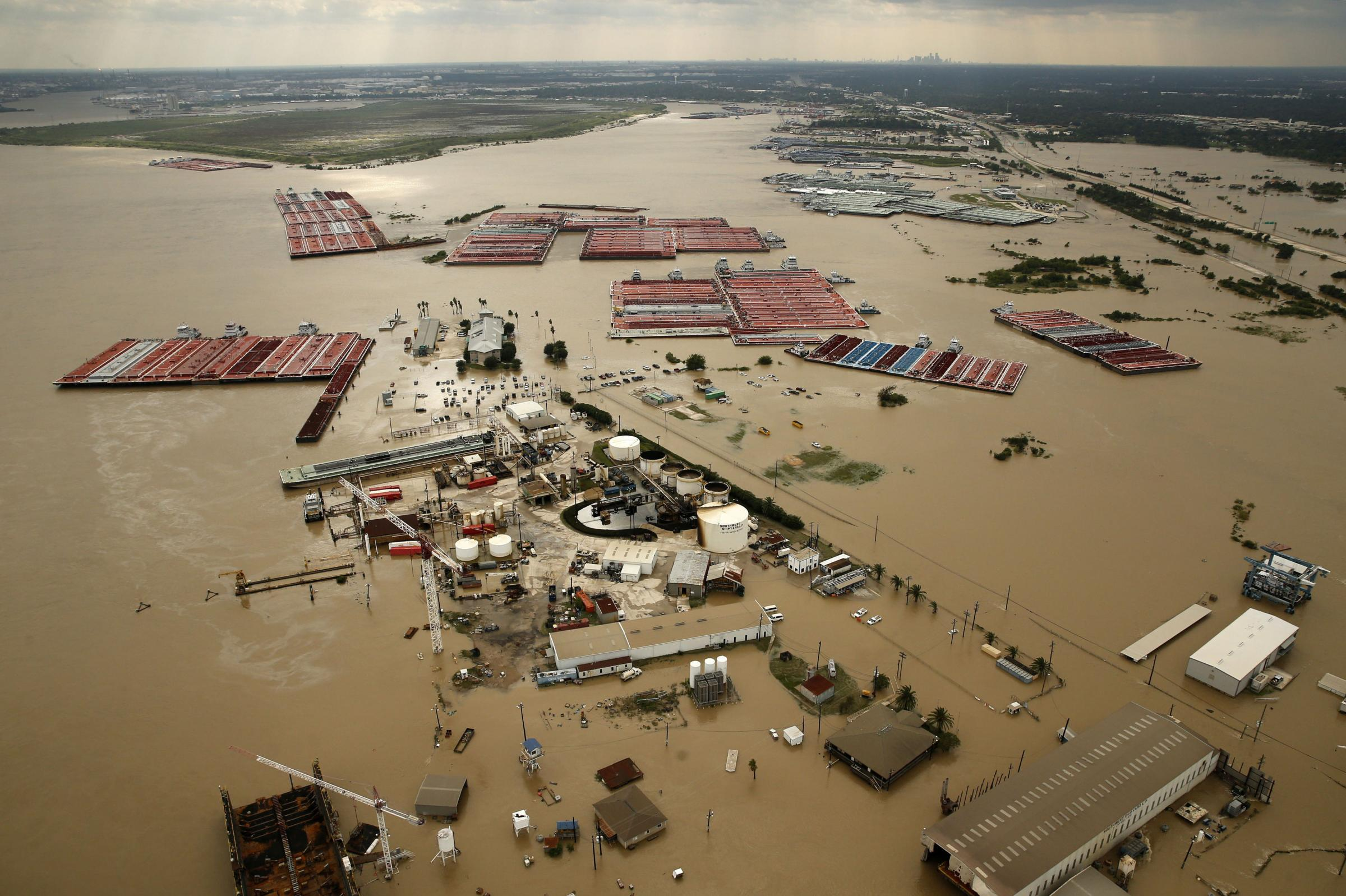 Barges are secured by tugboats in the flood-swollen Burnet Bay along the Houston Ship Channel