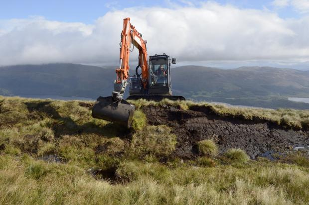 The National: Staff from Highland Conservation reprofiling peat hags at Beinn Dhuand Mid Hill. Pic Lorne Gill