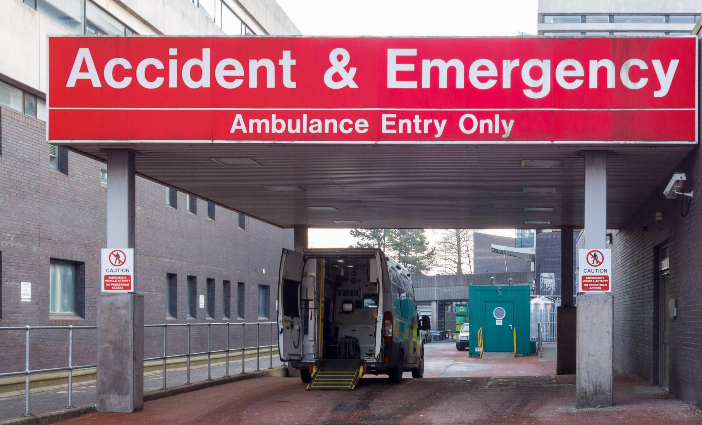Accident and Emergency hospital entrance with open ambulance parked outside - UK.
