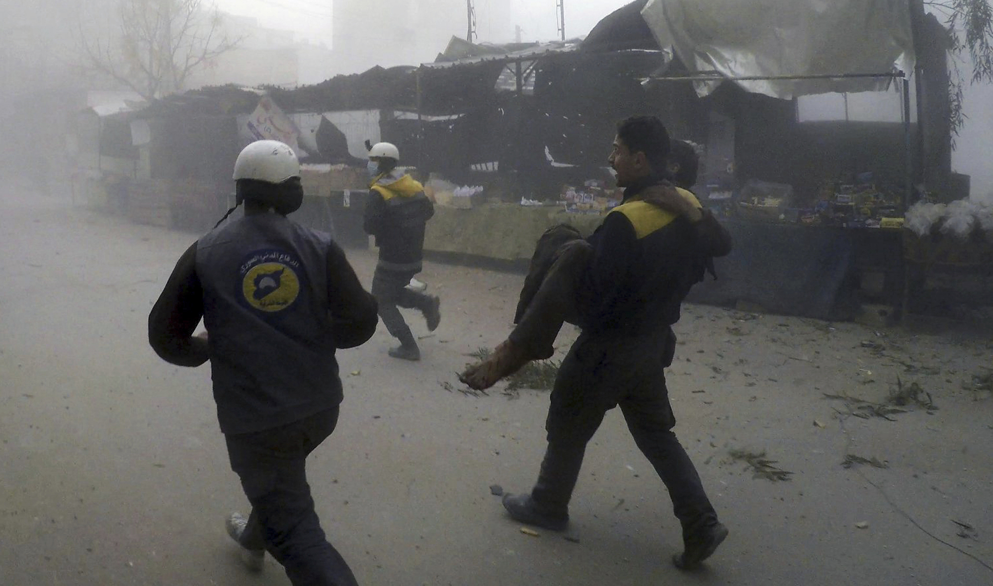 The White Helmets carry a man wounded by the attacks. Photograph: AP