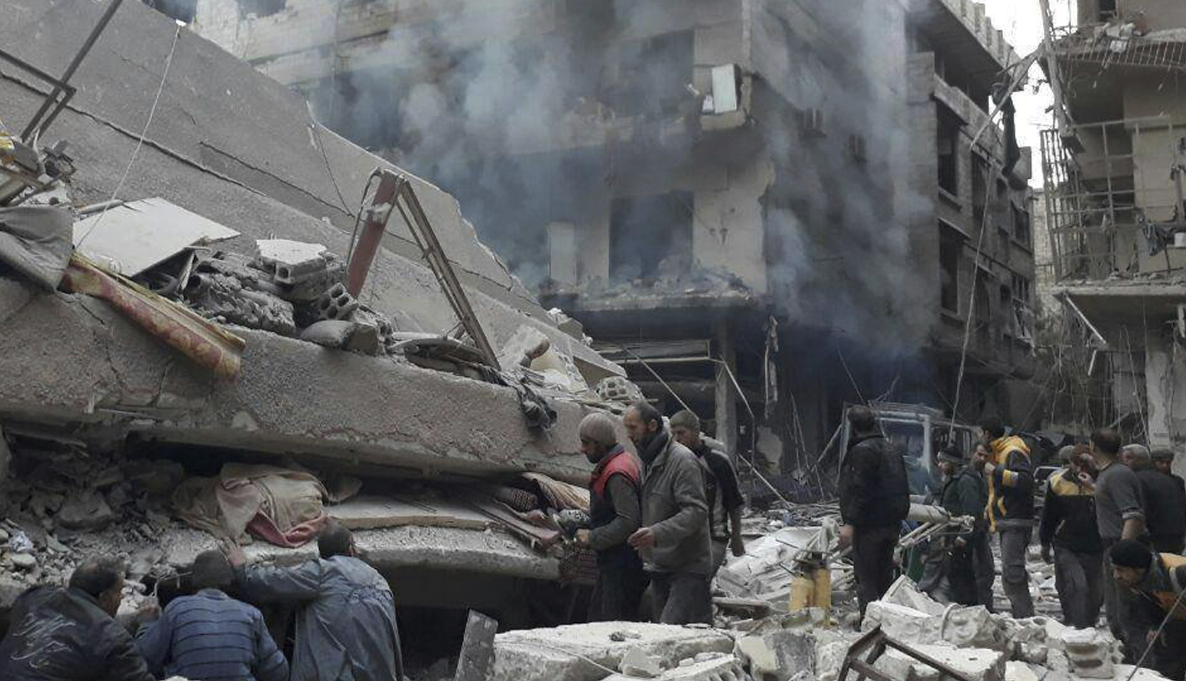 Syrians search for victims under the rubble of a destroyed building that attacked by Syrian government forces airstrikes in Ghouta. Photograph: AP