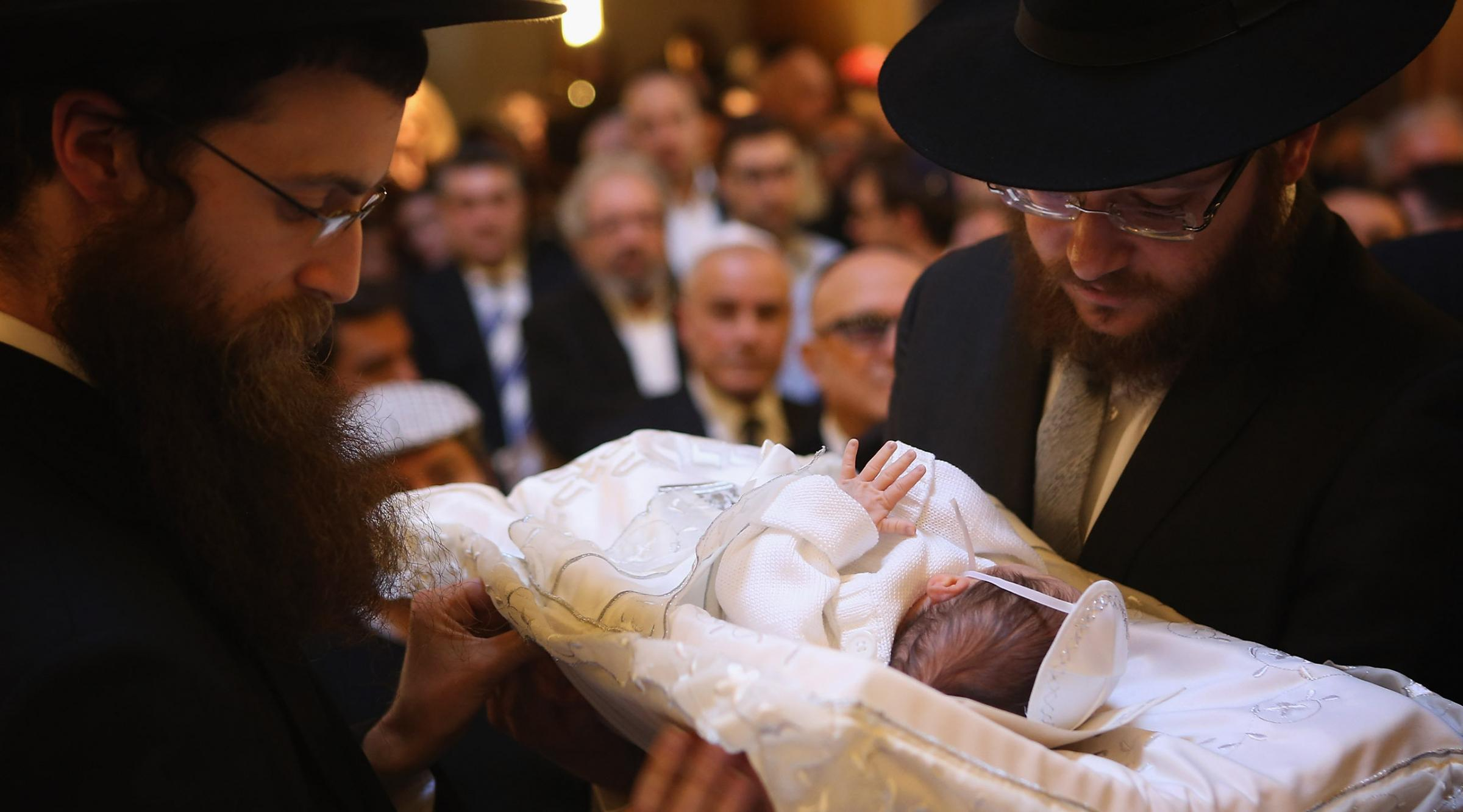 Orthodox Jews pass a baby infant to one another before his circumcision at the Chabad Lubawitsch Orthodox Jewish synagogue in Berlin, Germany