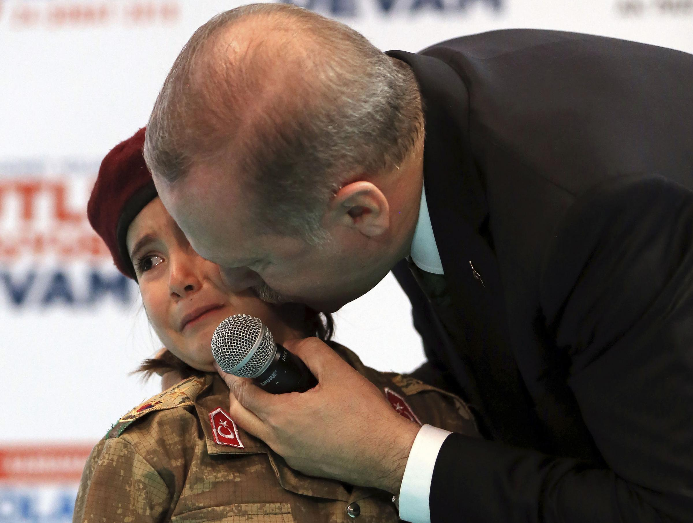 Turkish President Recep Tayyip Erdogan kisses Amine Tiras, a young girl in military uniform, as he speaks to his ruling party members in Kahramanmaras, Turkey