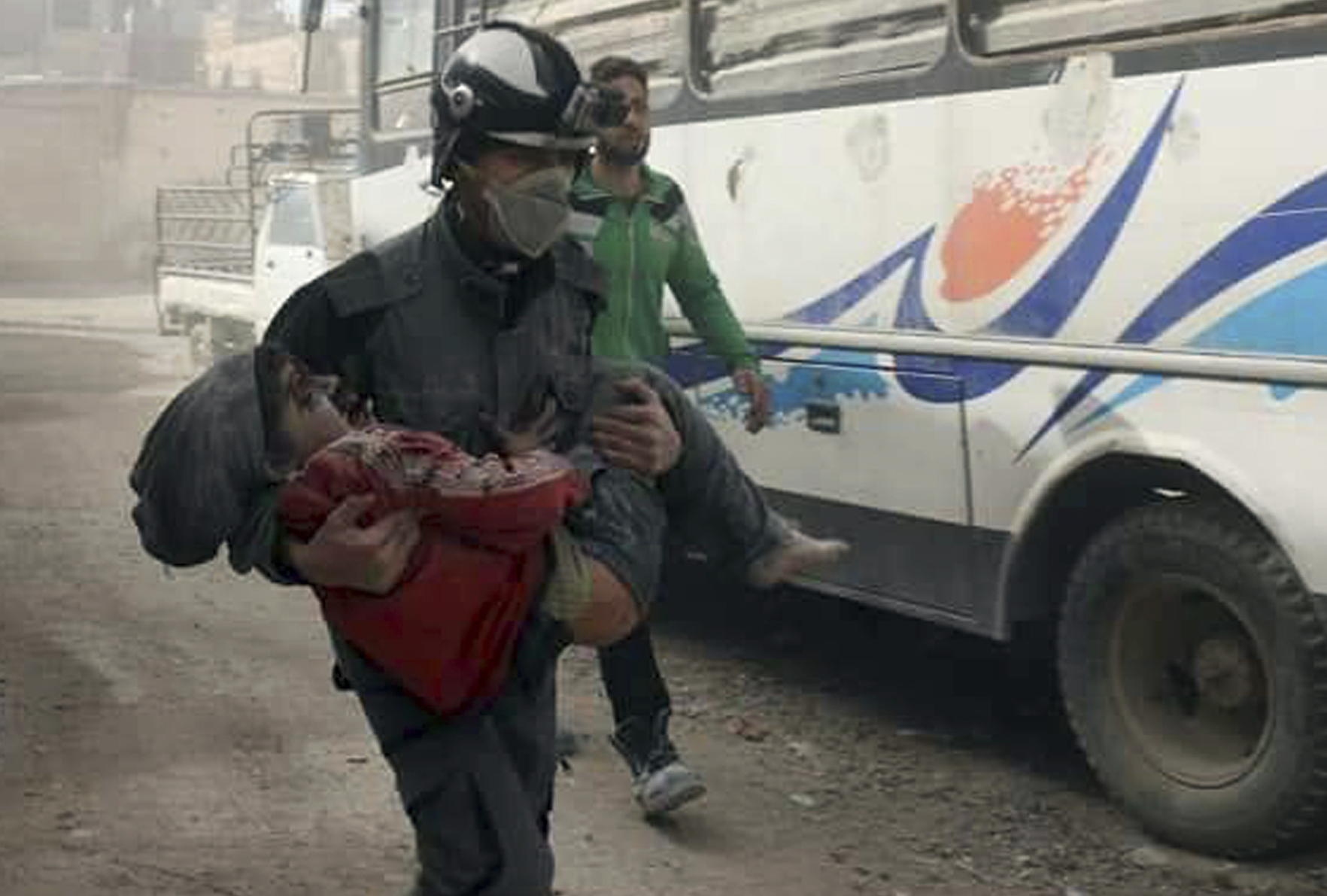 This photo provided by the Syrian Civil Defense White Helmets, which has been authenticated based on its contents and other AP reporting, shows a member of the Syrian Civil Defense group carrying a boy who was wounded during airstrikes and shelling by Syr