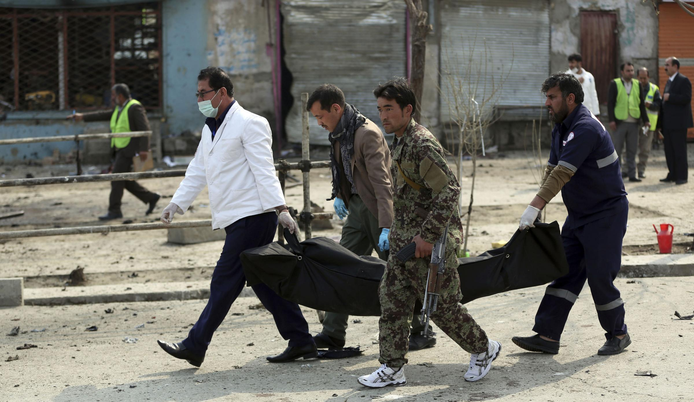 Security personnel carry a body at the site of a suicide attack in Kabul. Photograph: AP