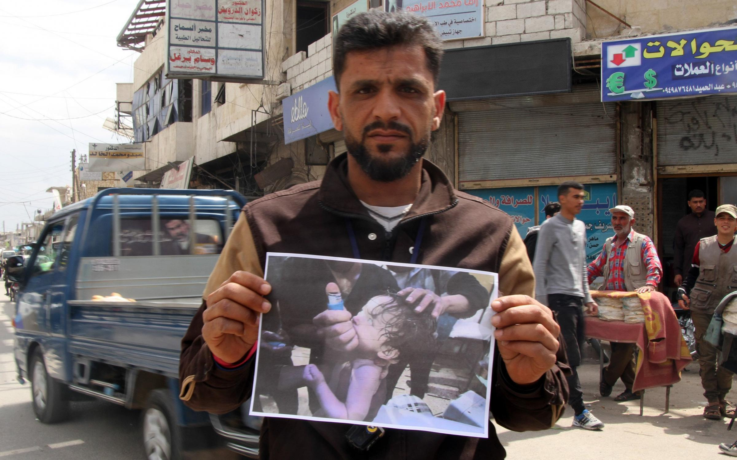 A man holds a photo of a baby as he and other demonstrators gather to protest against Assad regime forces' allegedly conducted poisonous gas attack on the town of Douma