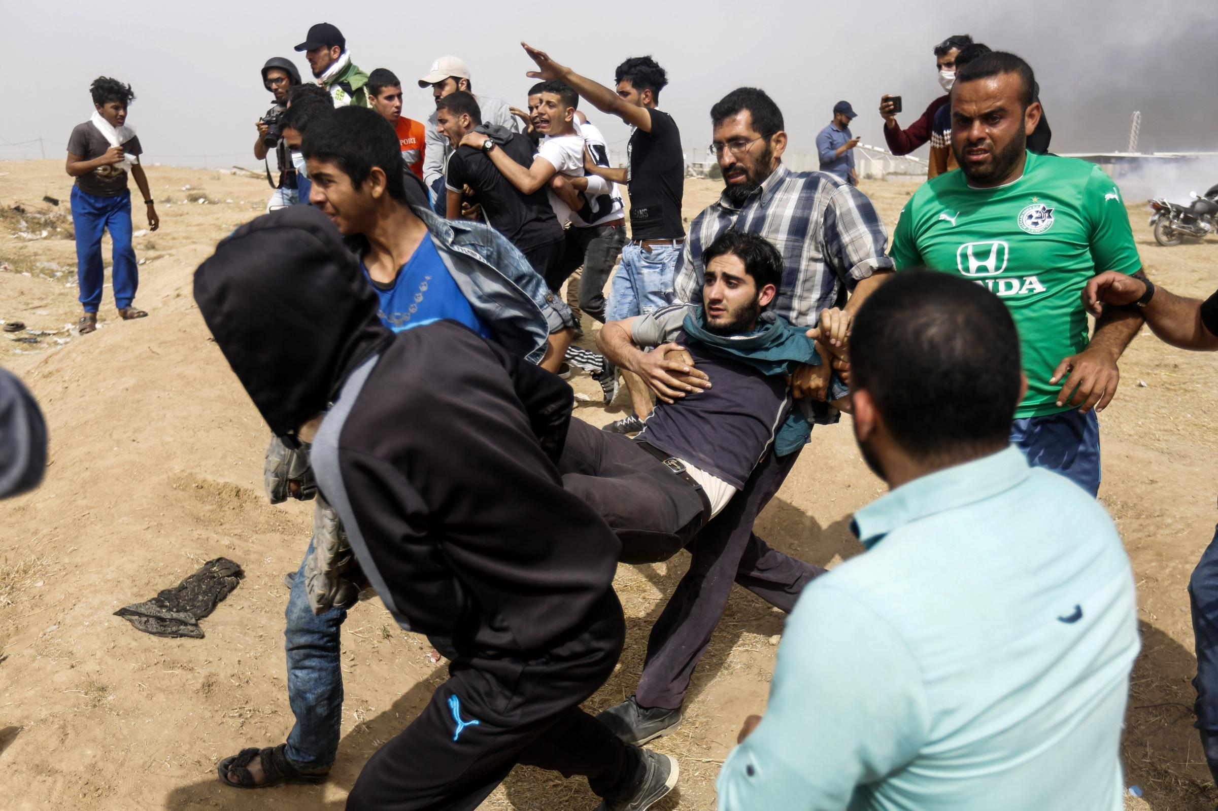 Palestinian protesters carry away a man injured during clashes with Israeli forces in the Gaza Strip