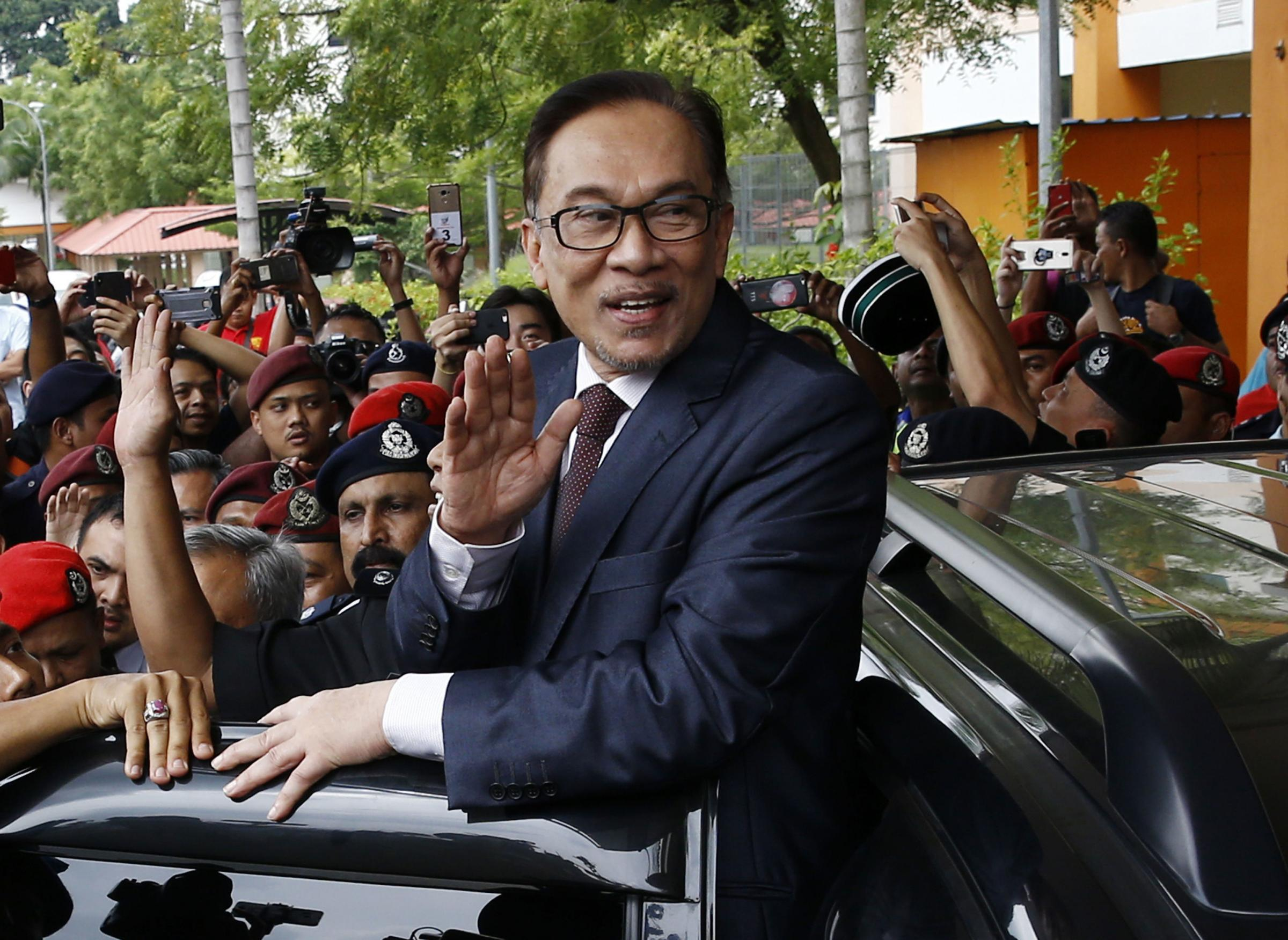 Malaysia's reformist icon Anwar Ibrahim waves to his supporters after leaving a hospital in Kuala Lumpur, Malaysia