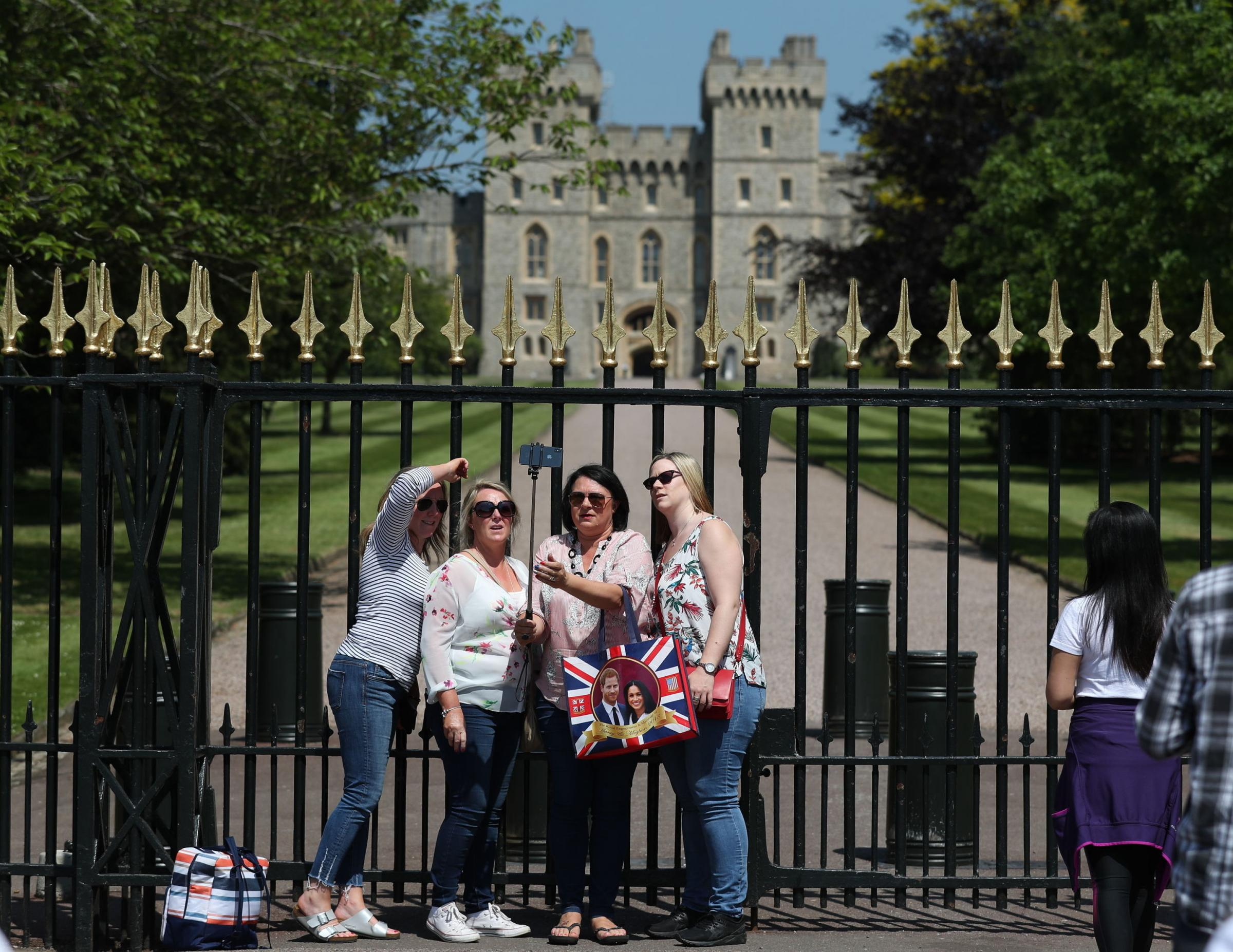 Royal fans pose for a selfie at the gates of Windsor Castle the day after the wedding of Prince Harry and Meghan Markle