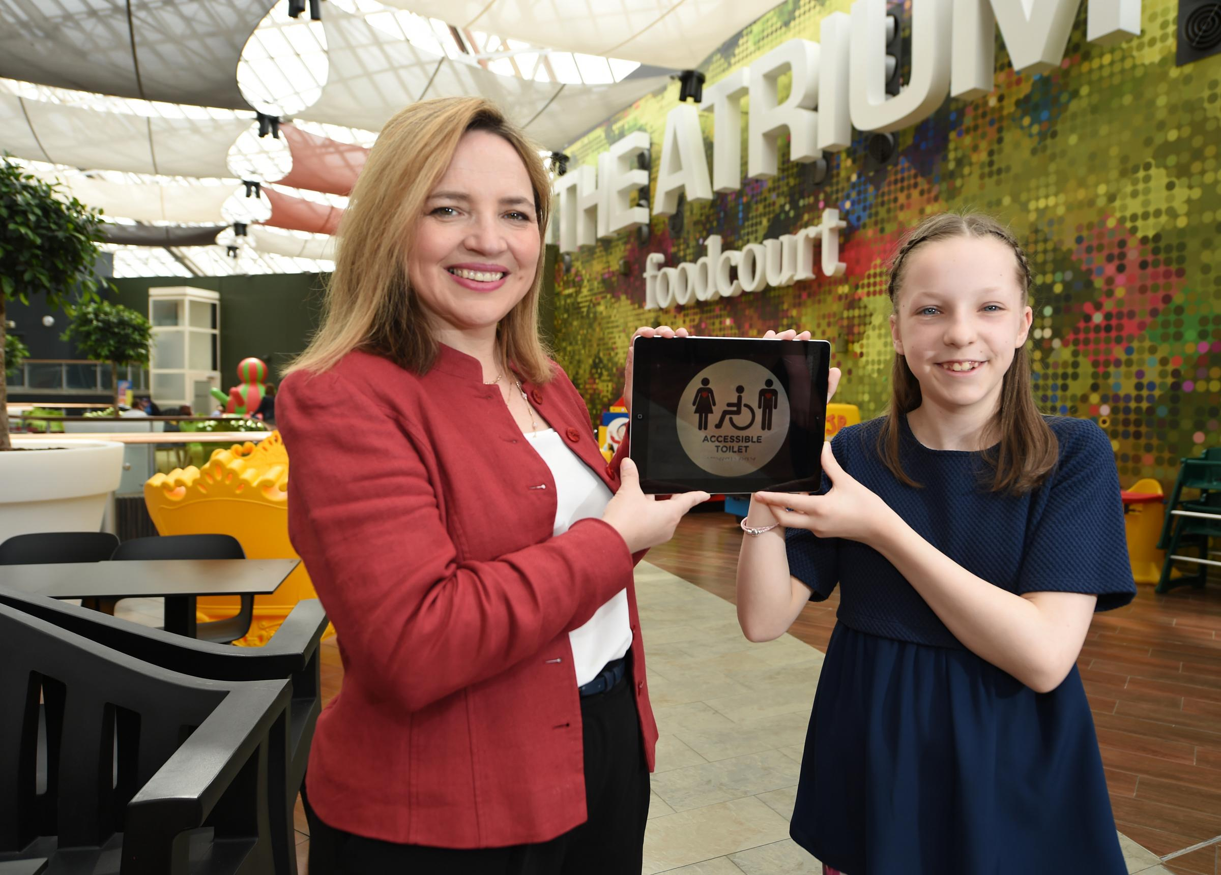 Anne Ledgerwood, general manager of St Enoch Centre, with 13-year-old Grace Warnock and a sign featuring her design